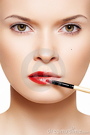 Lips make-up. Applyng red lipstick using lip brush