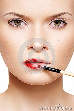 Lips make-up. Applyng red lipstick using lip brush