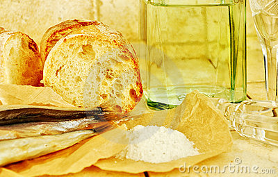 Liquid in a bottle, wineglasses, bread and salt