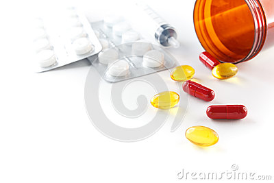 Liquid capsules and pills spilling out of bottle