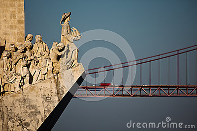 Lisbon Monument to Discoveries explorers statues with the 25th of April bridge Editorial Photography
