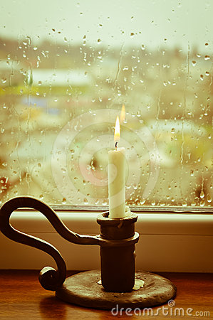 A lit candle on a rainy day