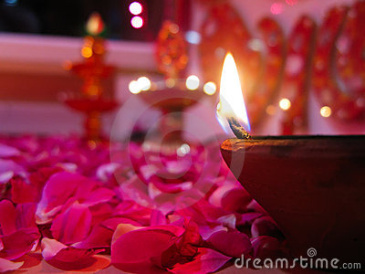 A lit diya on bed of roses