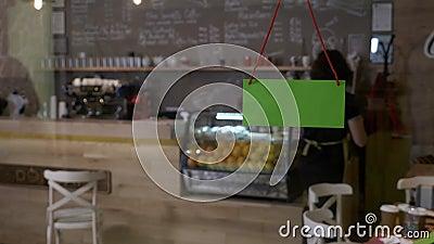 Liten coffee shopägare som bläddrar över öppet tecken för grön skärm på dörren i morgonhälsningklienterna och tar beställningar - lager videofilmer