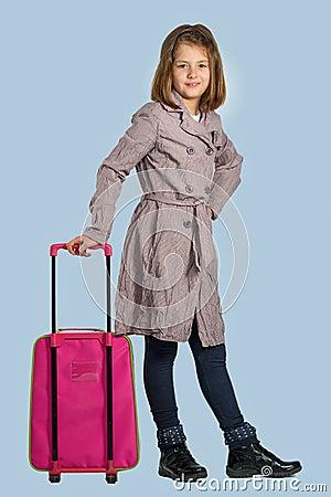 Liten flicka med en resväska förbereder sig att resa