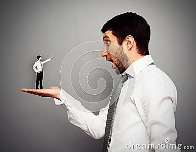 Liten man som pekar på den häpna stora mannen
