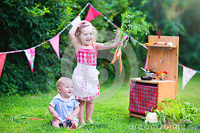 Little adorable kids playing with toy kitchen in the garden