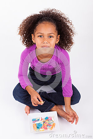 Little African Asian girl eating  candy