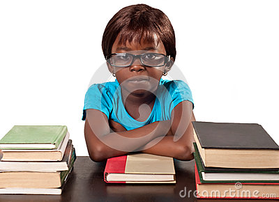 Little African school girl by stack of books