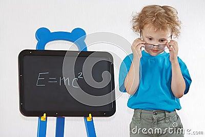 Little amazed boy with glasses shows formula