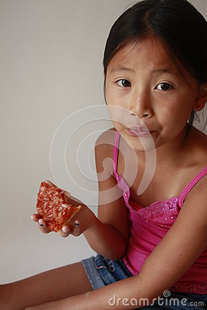 Little Asian girl eating pizza
