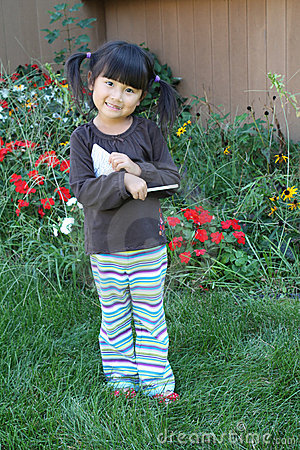 Little asian girl in garden taking notes