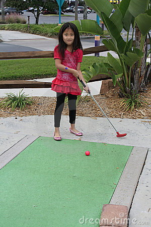 Little asian girl playing golf