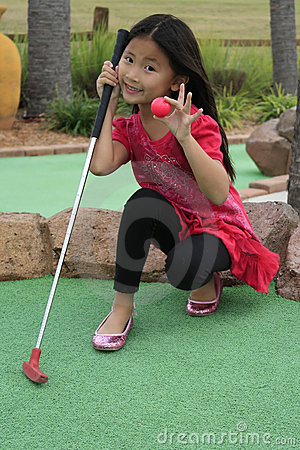 little asian girl playing mini golf