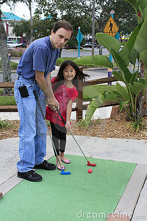 little asian girl playing mini golf with dad