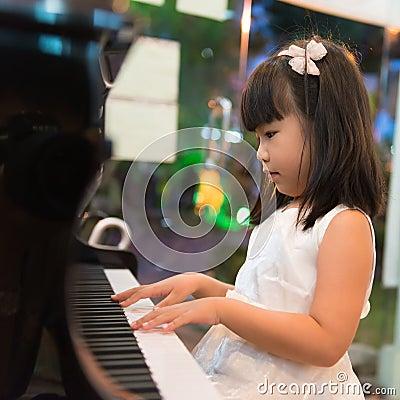 Little Asian girl playing piano