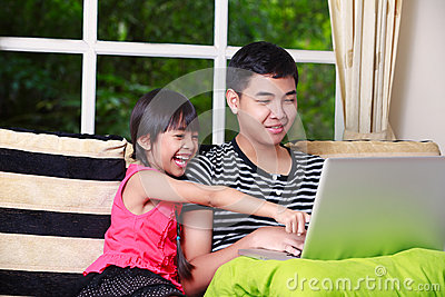 Little asian girl pointing on laptop with big brother