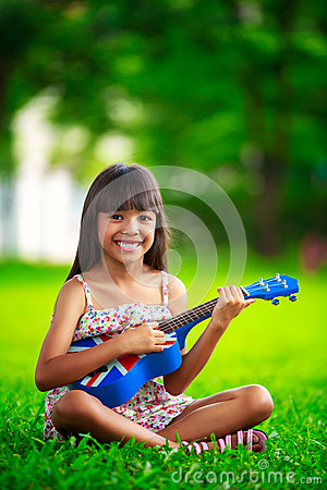 Little asian girl sitting on grass and play ukulele