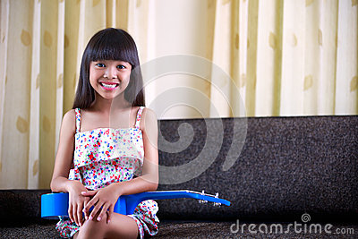 Little asian girl sitting with ukulele