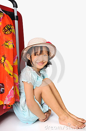 Little asian girl in weave hat sitting near a huge travel red su