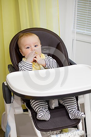 Free Little Baby Boy Sitting In Chair For Feeding And Eating Special Biscuit For Babies. Kitchen Royalty Free Stock Image - 118134016