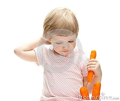 Little baby eating fresh carrot