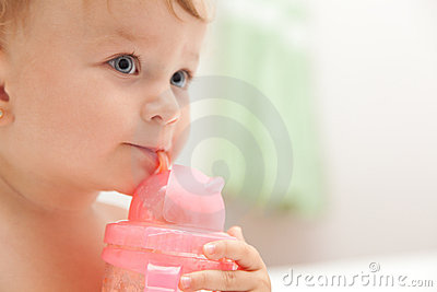 Little baby girl drinks juice from a bottle