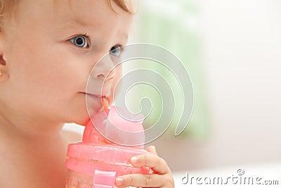 Little baby girl drinks juice from a bottle