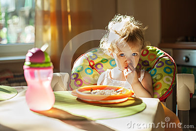 Little baby girl eating breakfast