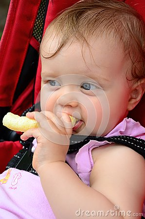 Little baby girl eating corn puff snack