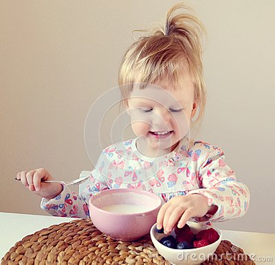 Free Little Baby Girl Eating Healthy Breakfast At Home, Berries And Yogurt Stock Photos - 105859113