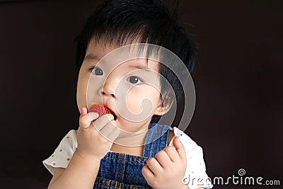 Little baby girl eating strawberry