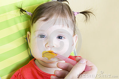 Little baby girl eating a vegetable puree