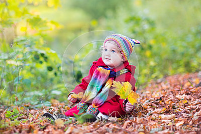 Little baby girl in park with golden maple leaves