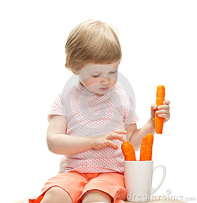 Little baby girl playing with fresh carrots