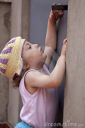 Little baby girl reaching for a door knob