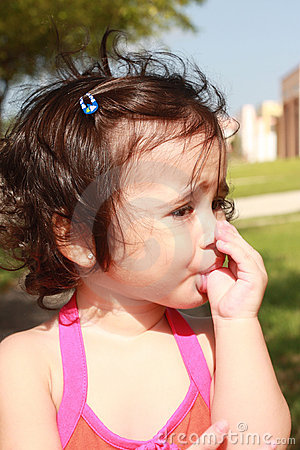 Little baby girl, sucking her thumb in the park