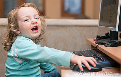 Little baby girl using a desktop computer, smiling