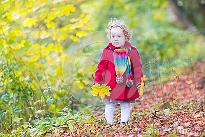 Little baby girl wearing red coat in autumn park