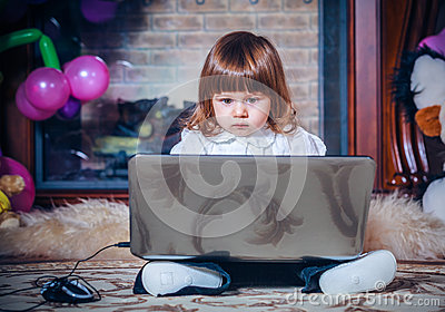 Little baby playing with laptop