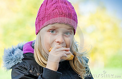 Little beautiful blond girl eating cake in park