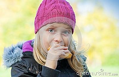 Little beautiful blond girl eating cake in park