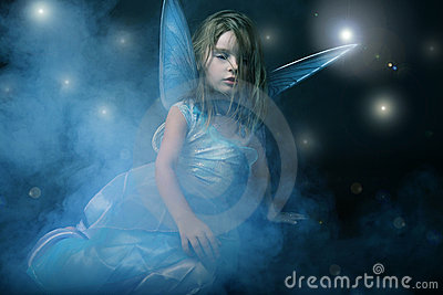 Little beautiful girl in blue dress with wings.