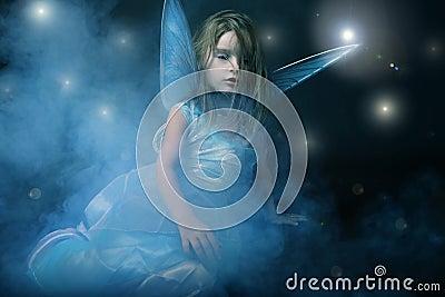 Little beautiful girl in blue dress with wings.