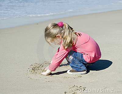 Little beautiful girl draws on sand