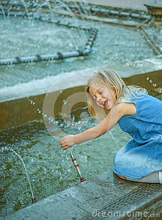 Little beautiful girl playing in fountain
