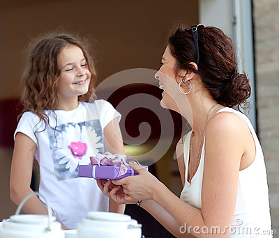 Little beautiful pretty girl giving a gift to her happy mother