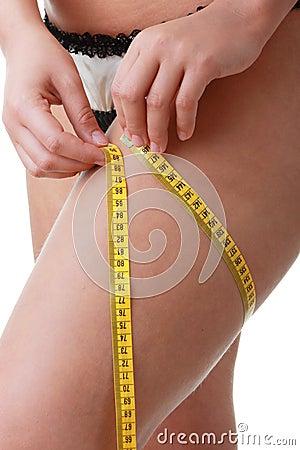 A little bit fat young woman mesuring her body