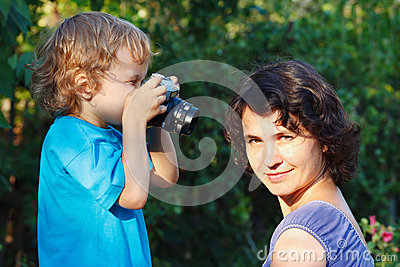 Little blond boy with a camera shoots her mother
