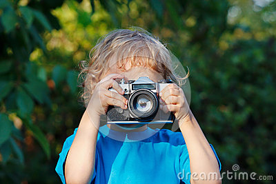 Little blond boy with a camera shoots you
